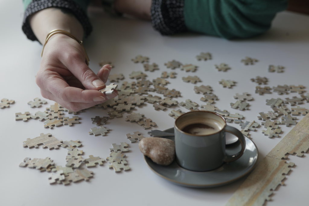 Image of a person working on a puzzle with a coffee